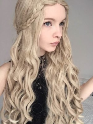 Blonde long curly wig. Thrones delivers beautiful long tumbling curls to the waist. In colours of light sandy blonde tones. The look is pulled together with a pre-styled braid, but that doesn't stop you from adding more if you wish. Perfect for reflecting the Daenerys Targaryen character from the series that inspired its name. Or for a natural bohemian look.