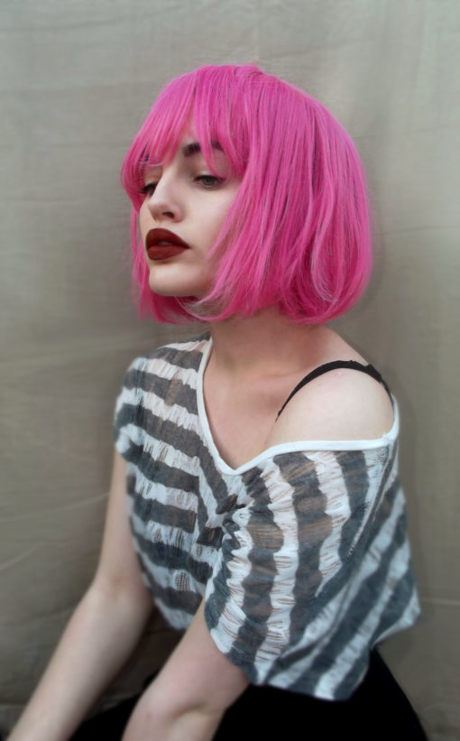 Cute bright pink bob wig with fringe. Milkshake brings us this vibrant fuscia pink colour, from roots to ends. A sleek graduated bob that falls just under the jawline. With a full fringe to add definition to the face. A style thats loud enough to stand on its own, or add intensity with accessories.