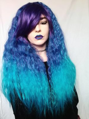 Purple and blue long wavy wig with bangs. Blueberry Fizz has amplified waves that produce this big, voluminous style. A concoction of purple roots thats carried into the fringe, sky blue melts into aqua dip-dyed tips. The long thick fringe add extra layers to the face.