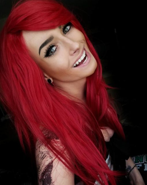 Red long wavy wig with bangs. Red Alert! Cherry Lipgloss is a waist length, bright cherry red colour from roots to tips. It is straight with long layers for body and movement. A long thick fringe can be worn as it is, or to add extra layers around the face.
