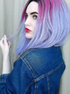 Pink and lilac straight lace front bob wig. Saturn is a cosmic play of vibrant hues. With a cast of warm black shadowed roots, that fade into a block of muted rose pink, then into a blue lilac ombre colour. Cut into an a-line graduated bob that falls just to the collarbone.