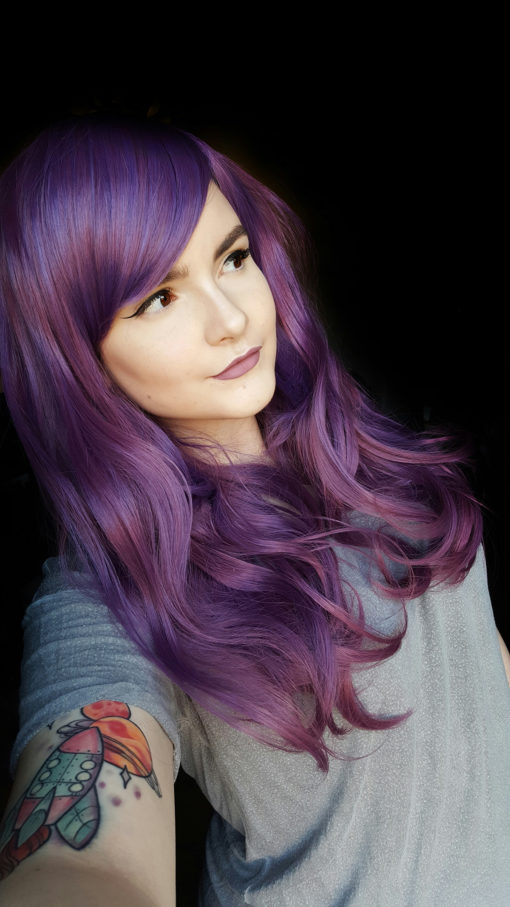 Purple long straight wig with bangs. Purple Haze is a distinctive deep purple shade. Styled in a Hime cut. The fringe frames the face in a blunt cut, and the front layers just fall to the jawline with a flick to their ends. The long lengths fall just past the shoulders and end with a curl.