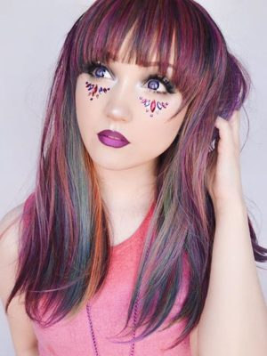 Multi colour long straight wig with bangs. Our dark side of the rainbow twist! A mixture of purples, pinks and green tones, blended with a deep red to bring it to life. Vivid colours transformed into muted tones, makes this a surprisingly wearable wig, this sleek style falls just past the shoulders and has a thick blunt fringe.