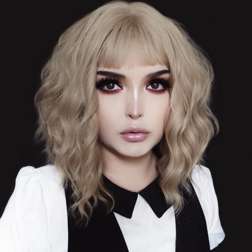 Blonde wavy bob wig with bangs. Milk Tea is a natural and simple style that comes in a light blonde shade, from roots to tips. Styled in loose beachy waves for texture, and a wispy fringe to frame the face. The lengths fall just above the shoulders. A classic bob thats easy to maintain.