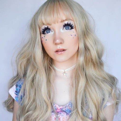 Long blonde with fringe wig. Callisto gives a cool and natural element to your look. A white blonde shade has a pearly, ethereal tone. Its styled with delicate waves that fall to the waist. Complete with a fringe to frame the face.