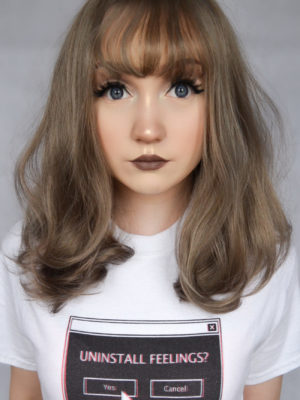 Grey curly wig with bangs. Sepia is silky, soft, and creates an effect of subtle fullness. A mixture of warm brown and ash blonde, from roots to tips, create this radiant look. sleek with curls at the ends to generate texture and movement. Falls just past the shoulders with a wispy fringe to frame the face.