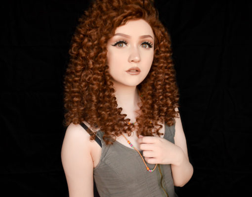 Golden brown spiral curls cut into a shoulder length style, Belle is a big and bold natural lace front. These tight curls fall in all directions, and with no defined parting they are free to be wild, or can be worn parted and tamed a little.