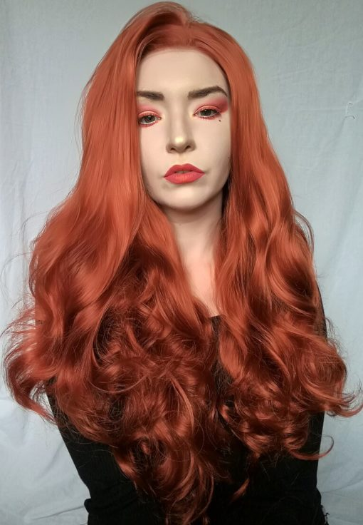 Orange red long curly lace front wig. Chilli is a bold concoction of colour with orange and red hues with a pinch of ginger. Its sleek from the roots then falls into curls that land at the waist. Add you own individuality with dressing and styling.