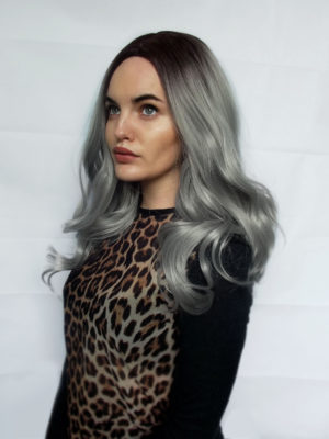 Grey long curly wig with dark roots. Penny captivates witchy vibes, with its warm black roots that have an undertone of deep purple. The silvery grey tones, carried through the locks of this style, brought into its own with loose curls that fall to the waist. Simple but eye catching with its unique hues. Dress up with braids or accessories to make it your own.