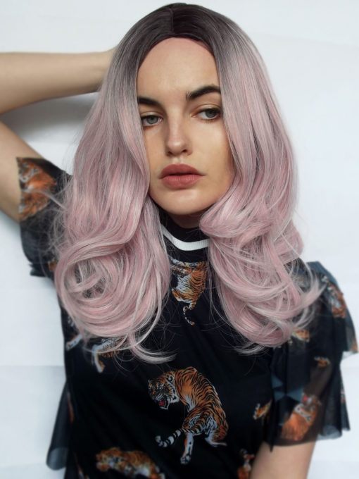 Pink long straight wig. Strawberry Shortcake is a cute blend of muted pastel pink. With cool black root shadows for an outgrown look. It falls in loose curls just past the shoulders. Finished in a blow-out technique, perfect for adding volume.