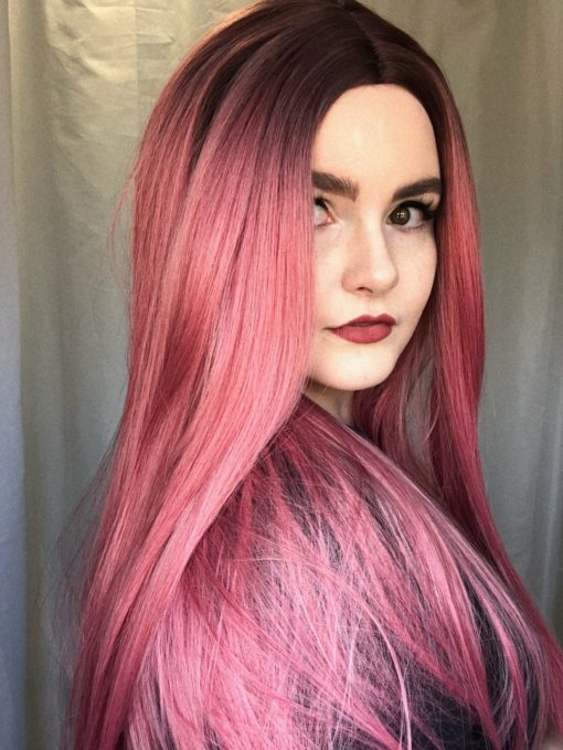 Pink straight long wig. Rhubarb delivers a contrast of sweet tones with its deep purple roots that melt into a rich rose pink colour to the ends. A classic straight and thick style, simple but never understated. Dress up with braids or accessories to make it your own.