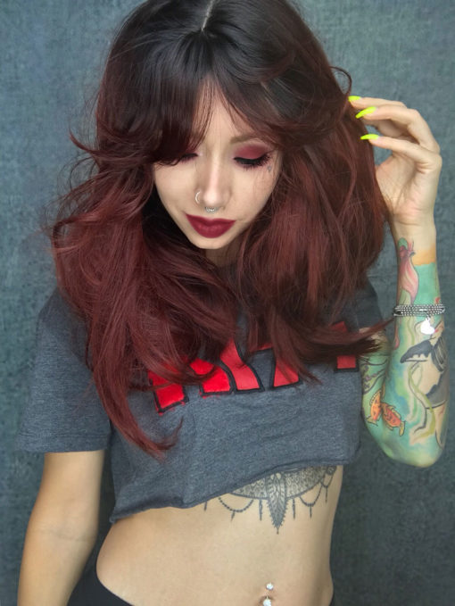 Muted red long straight wig with bangs. Blood moon has a mix of nocturnal colours. Black roots that melt into a deep muted cherry red ombre that's carried through the fringe. The sleek and thick texture falls to the waist. Add your own individuality with dressing and styling.