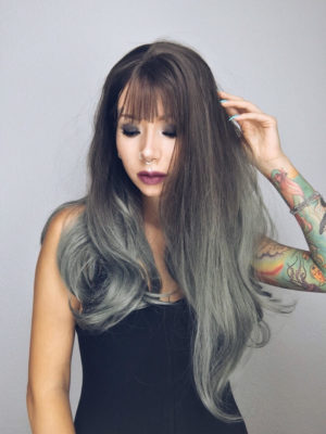 Dark green long straight wig with bangs. Sage is a mix of stunning brown roots with a deep, muted sage green ombre. The ombre comes in mid-way through sleek lengths, that fall to the waist. With a wispy fringe that compliments the finished blow-out style.