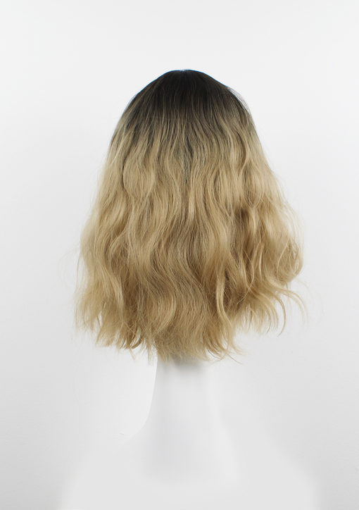 Blonde wavy long wig with bangs. Eleri is a staple natural addition to your look. Dark brown shadow roots blend into a light blonde hue. Giving the perfect grown-out look. We love this wavy style, it falls just below the shoulders with a fringe. And loose waves for volume. Easy to wear and maintain.