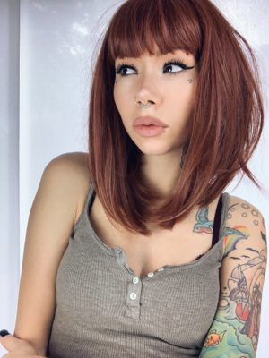 Brown straight long bob wig with bangs. Saffron is a natural granulated cut that falls just above the shoulders. A mixture of brunette and cinnamon undertones from roots to tips. A sleek long bob with a blunt fringe. A combination of stylish and sassy.