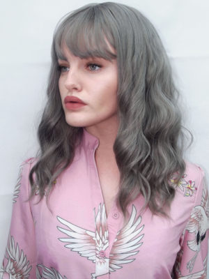 Grey wavy wig with bangs. Mist gives soft romantic gothic vibes. Tousled soft waves generate fullness. An unusual silvery grey with subtle golden highlights, from roots to ends makes it very natural. The wispy fringe frames the face.