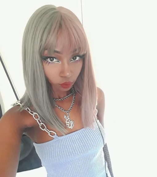 Half pink half grey split straight bob wig. Perish takes on the split colour technique with soft and subtle results. This gentle grey shade next to a rose soft pink. Split straight down the middle so the different colours fall either side of the centre parting. Styled straight and sleek with a fringe to frame the face that carries the split colour.