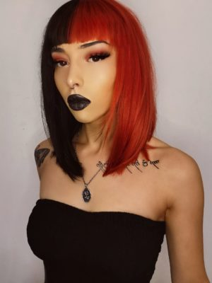 Half black half red spilt straight bob wig with bangs. High voltage takes on the dramatic colour divide. This super bold mix of red and black colours. Split down the centre parting and carrying the colour through the fringe. Styled sleek from roots to tips. Falling just below the collarbone. Easy to wear and maintain.