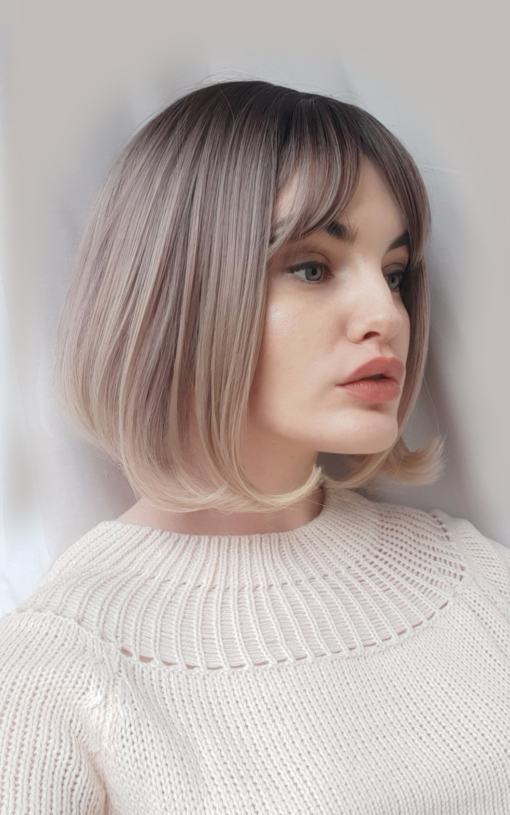 Blonde straight wig with bangs. Amai plays with pink undertones to create a soft and subtle mixture of dusky pinks. A natural twist of brown roots blend into this ombre with honey blonde ends. A short sleek style that curls under to meet the shoulders. Easy to maintain and carefree.