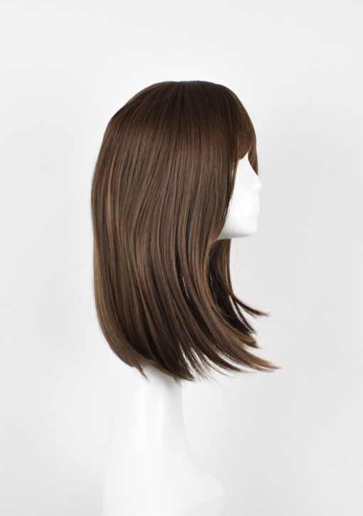 Brown natural straight wig with bangs. Kora is one of our natural and simple looks. The graduated cut falls perfectly just below the shoulders. Warm brunette colour.